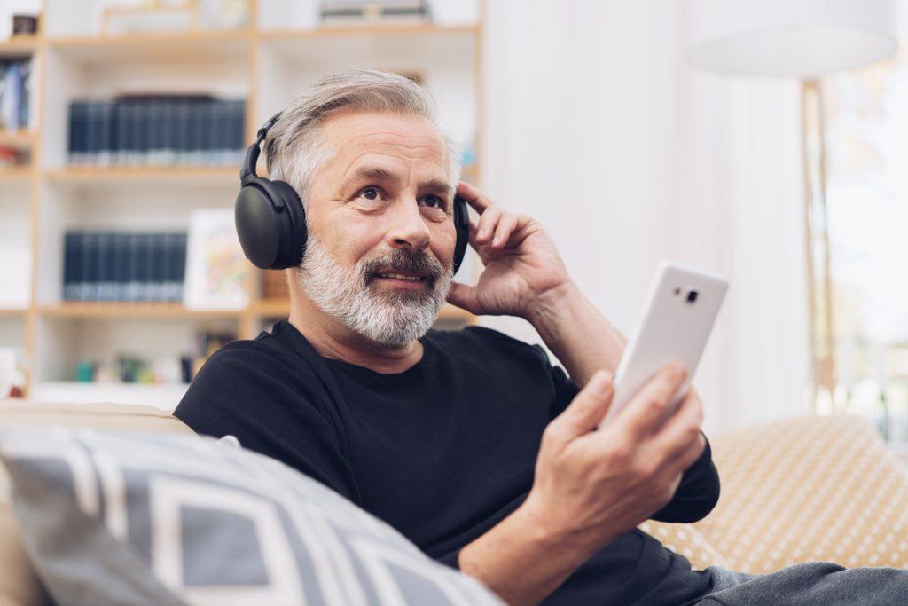 Kuva keski-ikäisestä miehestä kuuntelemassa äänikirjaa älypuhelimellaan.
