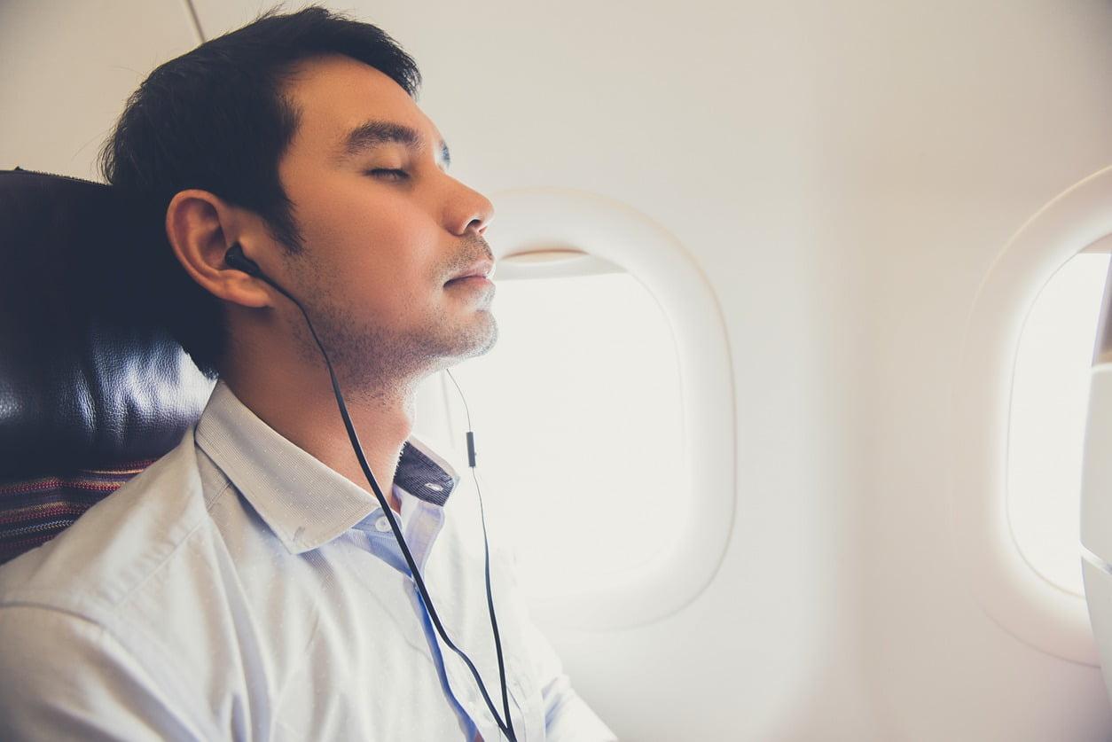 Kuva kauluspaidassa olevasta rentoutuneesta miehestä kuuntelemassa äänikirjaa lentokoneessa.