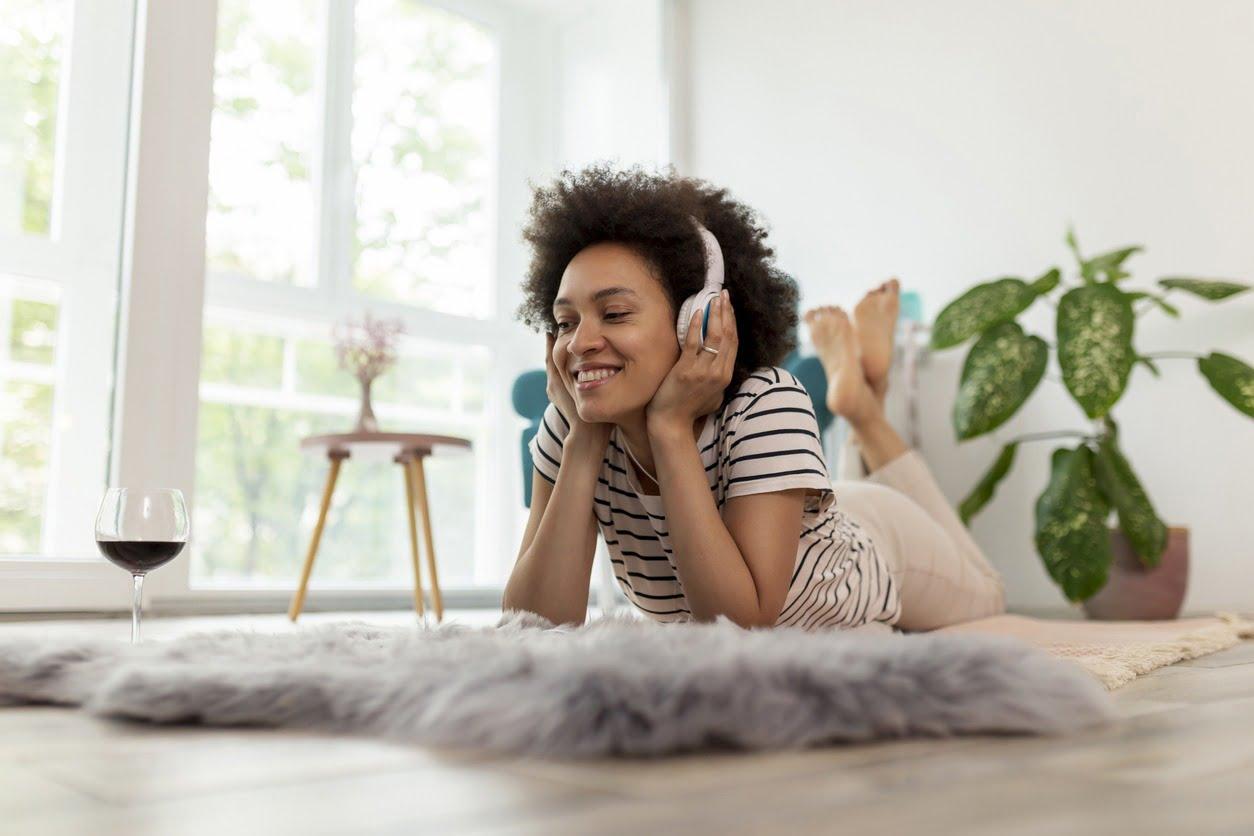 Kuva nuoresta naisesta kuuntelemassa äänikirjaa matolla maaten ja nauttien samalla viinistä.