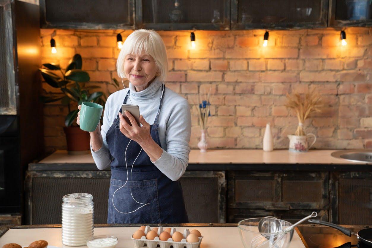 Kuva vanhemmasta naisesta laittamassa ruokaa samalla äänikirjaa kuunnellen.